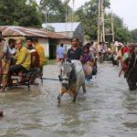 People move along a flooded road in Gaibandha, Bangladesh July 18, 2019. REUTERS/Stringer NO RESALES. NO ARCHIVES